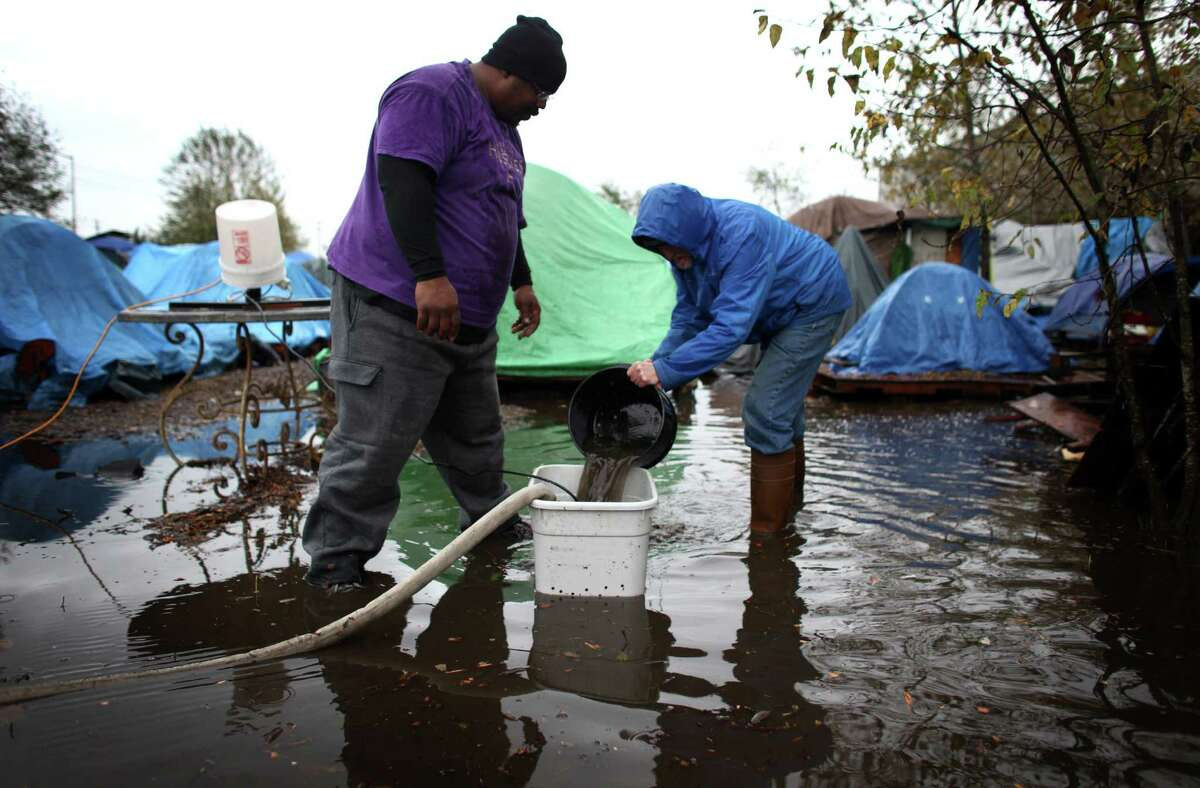 Nickelsville residents work to remove water from the homeless camp after record rainfall flooded Nickelsville homeless camp at 7116 West Marginal Way South. Tents and the pallets they rested on were floating after the camp filled with up to one foot of water after Monday's record rain. Photographed on Tuesday, November 20, 2012.