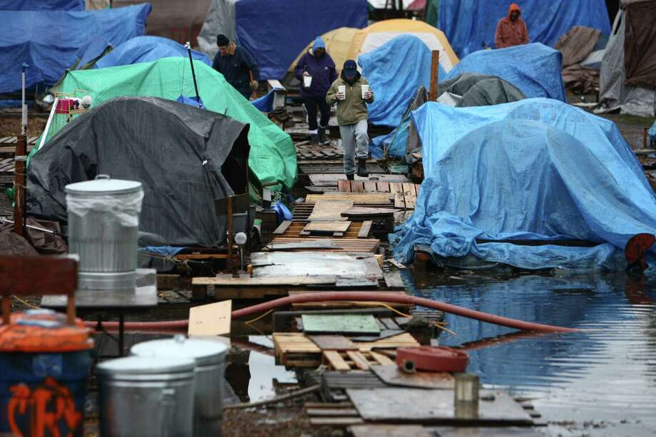 Nickelsville residents walk through the homeless camp after record rainfall flooded Nickelsville homeless camp at 7116 West Marginal Way South. Tents and the pallets they rested on were floating after the camp filled with up to one foot of water after Monday's record rain. Photographed on Tuesday, November 20, 2012. Photo: JOSHUA TRUJILLO / SEATTLEPI.COM