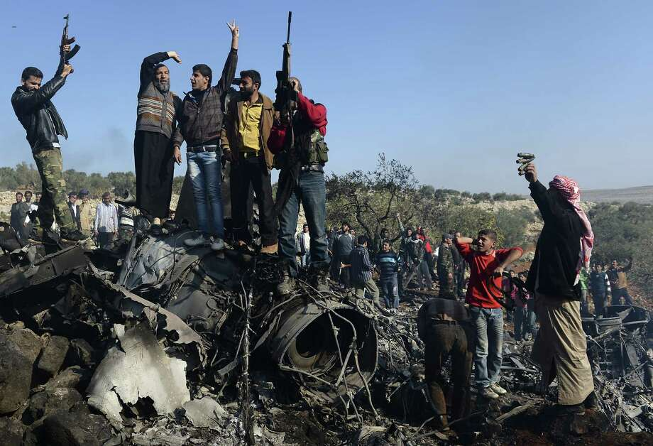 Syrian rebels celebrate Wednesday on top of the remains of a Syrian government fighter jet.  Western officials say the warplane and a helicopter may have been downed by shoulder-fired missiles, a new key element in the uprising. Photo: FRANCISCO LEONG, Stringer / AFP