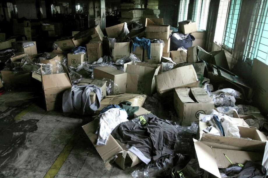 Boxes of garments lay near equipment charred in the fire that killed 112 workers Saturday at the Tazreen Fashions Ltd. factory,on the outskirts of Dhaha, Bangladesh, Wednesday, Nov. 28, 2012. Garments and documents left behind in the factory show it was used by a host of major American and European retailers, though at least one of them ? Wal-Mart ? had been aware of safety problems. Wal-Mart blames a supplier for using Tazreen Fashions without its knowledge. (AP Photo/Ashraful Alam Tito) Photo: Ashraful Alam Tito, STR / AP
