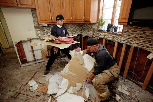 New York firefighter John Militano, left, and New Orleans firefighter Bruce Hurley, Sr. clear sheetrock from a gutted kitchen, flooded in Superstorm Sandy, in the Belle Harbor section of Queens, N.Y., Wednesday, Nov. 28, 2012. The New Orleans Fire Department is returning the help given to Louisiana after Hurricane Katrina by firefighters and other emergency workers from New York. Photo: Mark Lennihan, Associated Press / AP