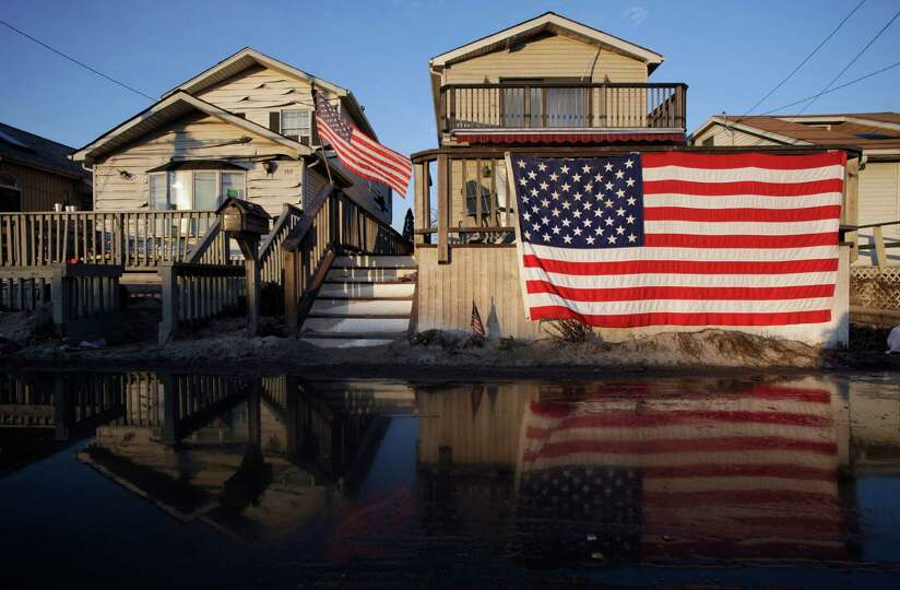 American flags are displayed on flood-damaged homes in the Breezy Point section of Queens, N.Y., Wed