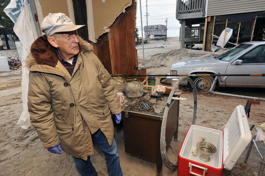 Walter Narkiewicz looks over recaptured fine china in the damaged garage section of his house on Jacqueline Avenue, Tuesday Nov. 27, 2012, in the Holgate section of Long Beach Township, N.J. Residents were allowed to permanently return to Holgate today, although many of the homes are not inhabitable following Superstorm Sandy. Photo: Michael Ein, Associated Press / The Press of Atlantic City