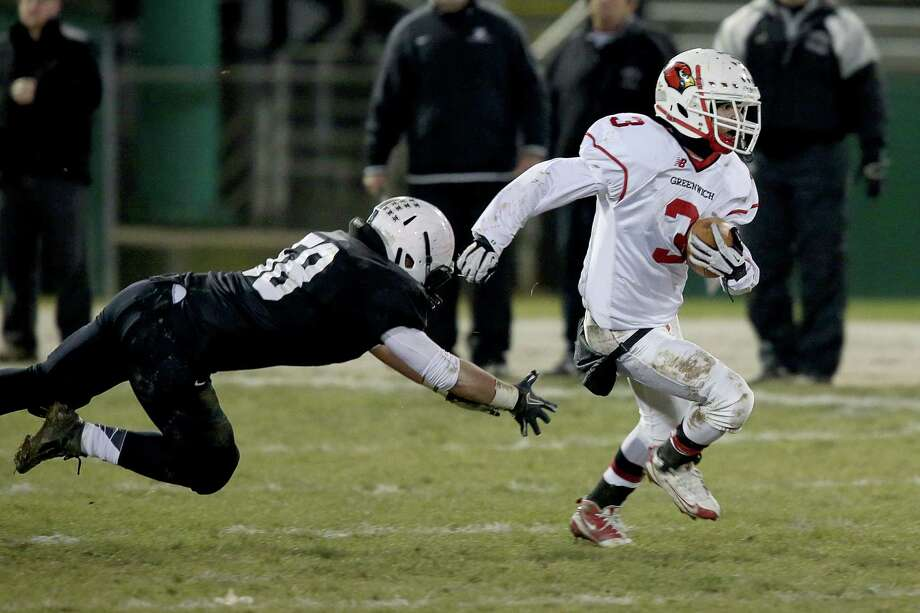 Mike Ross Connecticut Post freelance -Greenwich High School's # 3 Austin Longi escapes a tackle and makes a 67 yard touchdown run during Wednesday evening Class LL football quarterfinals against Xavier. Photo: Mike Ross / Connecticut Post Freelance