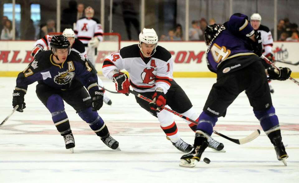 Albany Devil's Adam Henrique (14), center, goes for a loose puck as Manchester Monarch's Thomas Hick