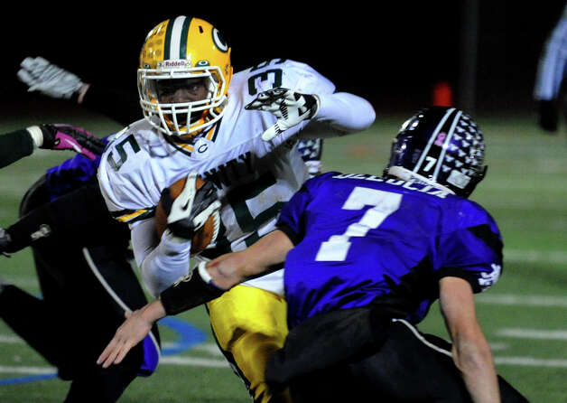 Trinity Catholic's #35 Sean Brown evades North Branford's #7 Joe Delucia, during CIAC Class S boys football quarterfinal action in Guilford, Conn. on Wednesday November 28, 2012. Photo: Christian Abraham / Connecticut Post
