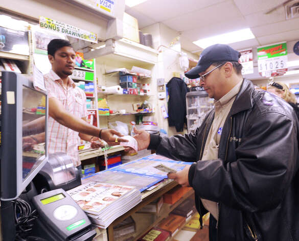 At right, Raul Lopez of the Bronx, N.Y., buys Powerball lottery tickets from Kartik Patel of the Greenwich Cigar Store on Railroad Avenue, Wednesday afternoon, Nov. 28, 2012. The jackpot for the lottery exceeded $550 million. Photo: Bob Luckey / Greenwich Time
