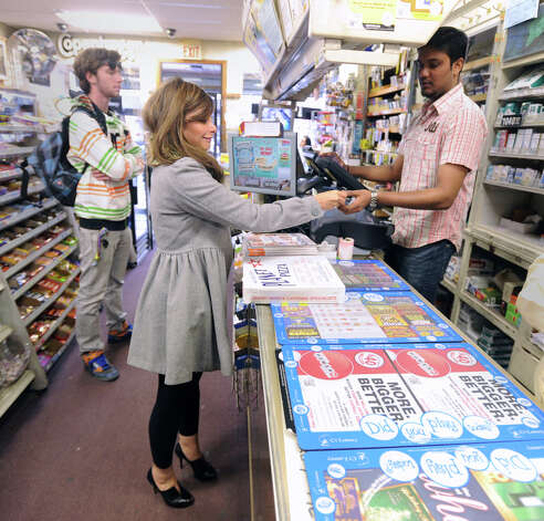 At center, Hina Pervez-Nigro of White Plains, N.Y., buys Powerball lottery tickets from Kartik Patel of the Greenwich Cigar Store on Railroad Avenue, Wednesday afternoon, Nov. 28, 2012. The jackpot for the lottery exceeded $550 million. Photo: Bob Luckey / Greenwich Time