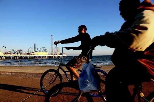 Bicyclist enjoy a ride on the boardwalk near the Pleasure Pier in Galveston. Photo: Thomas B. Shea, For The Chronicle / © 2012 Thomas B. Shea