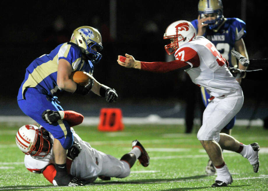 Newtown's Cooper Gold is brought down by Norwich Free Academy's Tuzar Skipper with help from Ryan Stowe, right, during their Class LL state quarterfinal game at Newtown High School on Wednesday, Nov. 28, 2012. N.F.A. won, 63-21. Photo: Jason Rearick / The News-Times