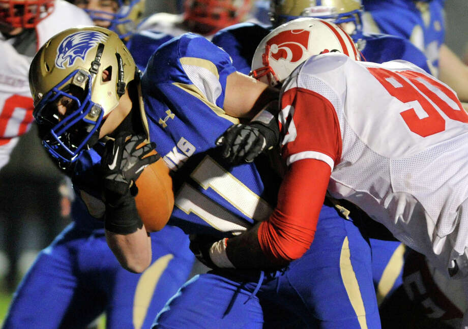 Newtown's Cooper Gold runs while being grabbed by Norwich Free Academy's Tuzar Skipper during their Class LL state quarterfinal game at Newtown High School on Wednesday, Nov. 28, 2012. N.F.A. won, 63-21. Photo: Jason Rearick / The News-Times