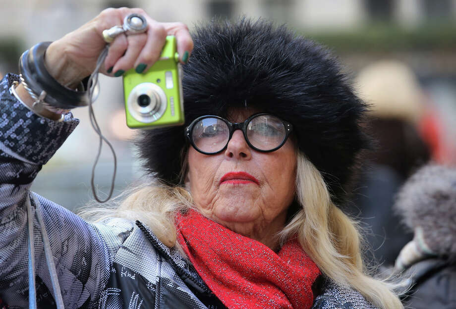 NEW YORK, NY - NOVEMBER 28:  Sheila Hogue, a tourist from Pensacola, Florida snaps photos as preparations are made for the lighting of the Christmas tree at Rockefeller Center on November 28, 2012 in New York City. After two weeks of preparation, the 45,000 lights will be lit on the 80-foot high Norwegian spruce this evening during a celebration televised on NBC and hosted by Al Roker and Savannah Guthrie. The tree will remain lit every evening until January 7.  (Photo by John Moore/Getty Images) Photo: John Moore, Getty Images / Getty Images