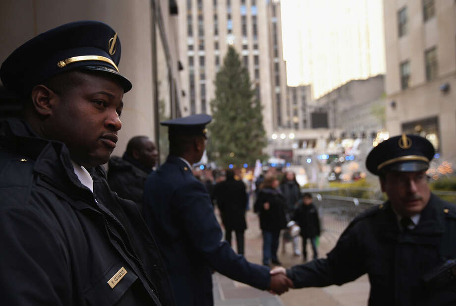 NEW YORK, NY - NOVEMBER 28:  Doormen stand by as preparations are made for the lighting of the Christmas tree at Rockefeller Center on November 28, 2012 in New York City. After two weeks of preparation, the 45,000 lights will be lit on the 80-foot high Norwegian spruce this evening during a celebration televised on NBC and hosted by Al Roker and Savannah Guthrie. The tree will remain lit every evening until January 7.  (Photo by John Moore/Getty Images) Photo: John Moore, Getty Images / Getty Images