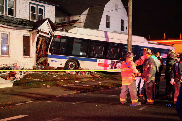Firemen work the scene where a  Nassau County bus, attempting to avoid hitting a pedestrian, crashed into a multifamily house, killing David Granados, 6, in a front bedroom, and injuring his older brother, Tuesday, Nov. 27, 2012, in Hempstead, New York. The boy and his 7-year-old brother were in the front bedroom of the house when the bus hit the pedestrian before plowing into the house, police said. The brother and pedestrian suffered non life threatening injuries. (AP Photo/Newsday, Howard Schnapp) NEW YORK OUT Photo: Howard Schnapp