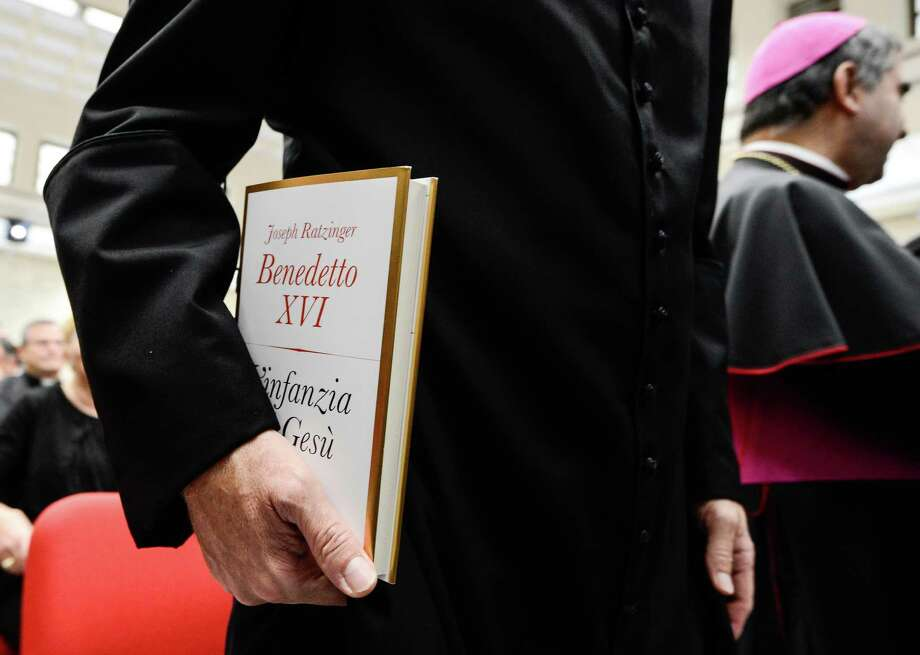 "Pope Benedict XVI's personal secretary Georg Gaenswein holds the pontif's new book ""Childhood of Jesus"" during the presentation of the book to the press on November 20, 2012 at the Vatican.  ""Childhood of Jesus"" is the third volume of Joseph Ratzinger's ""Jesus of Nazareth"" series. AFP PHOTO / ANDREAS  SOLAROANDREAS SOLARO/AFP/Getty Images Photo: ANDREAS SOLARO, AFP/Getty Images / AFP"