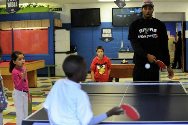 Kahwi Leonard of the San Antonio Spurs plays table tennis with children at the Eastside Branch of the Boys & Girls Club on Wednesday, Nov. 28. Leonard and teammate Stephen Jackson visited the club. Photo: Billy Calzada, San Antonio Express-News / SAN ANTONIO EXPRESS-NEWS
