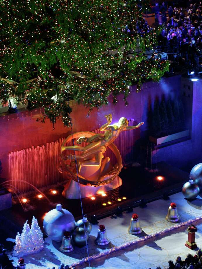 The statue of Prometheus stands underneath the Rockefeller Center Christmas Tree during the 80th annual tree lighting ceremony at Rockefeller Center in New York, Wednesday, Nov. 28, 2012. (AP Photo/Kathy Willens) Photo: Kathy Willens, Associated Press / Associated Press