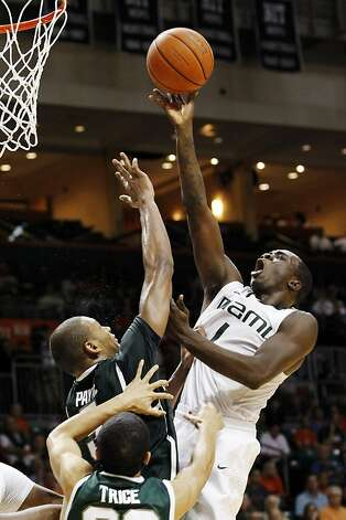 Durand Scott drives in Miami's victory over Michigan State. Photo: Alan Diaz, Associated Press