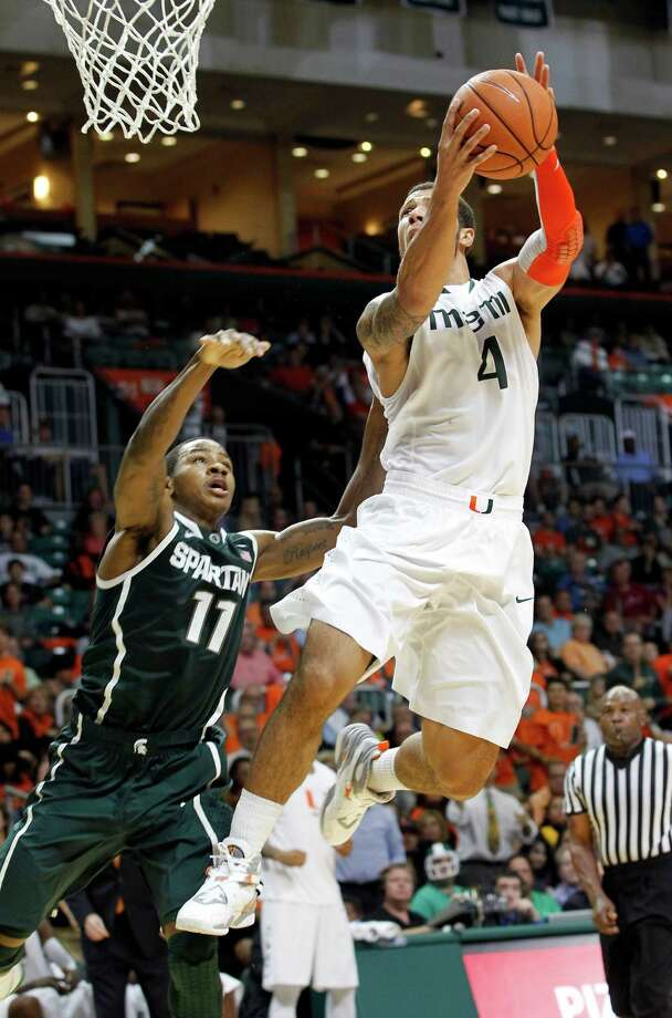 Miami's Trey McKinney Jones (4) prepares to shoot as Michigan State's Keith Appling (11) defends in the second half of an NCAA college basketball game on Wednesday, Nov. 28, 2012, in Coral Gables, Fla. Miami won 67-59. (AP Photo/Alan Diaz) Photo: Alan Diaz
