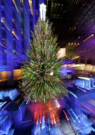 In this photo made using a zoom and slow exposure, the Rockefeller Center Christmas Tree is lit during the 80th annual tree lighting ceremony at Rockefeller Center in New York, Wednesday, Nov. 28, 2012.  (AP Photo/Kathy Willens) Photo: Kathy Willens, Associated Press / Associated Press