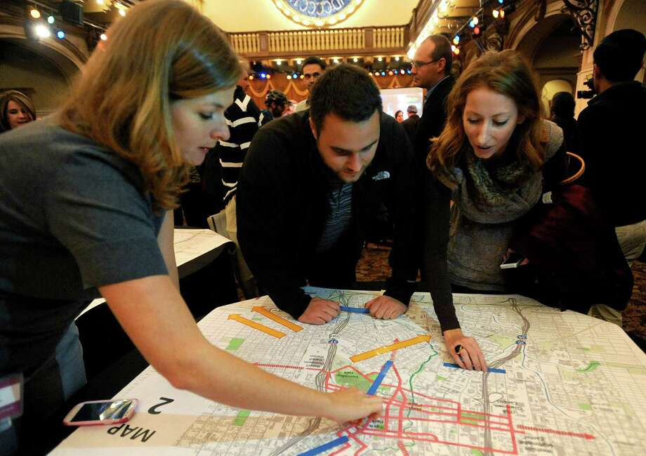 Abigal Kinnison, left, a planner with VIA Metropolitan Transit, receives feedback about the proposed modern street car project from Brian Smith and Melissa Unsell during a public meeting at Sunset Station on Wednesday, Nov. 28, 2012. Photo: Billy Calzada, San Antonio Express-News / SAN ANTONIO EXPRESS-NEWS