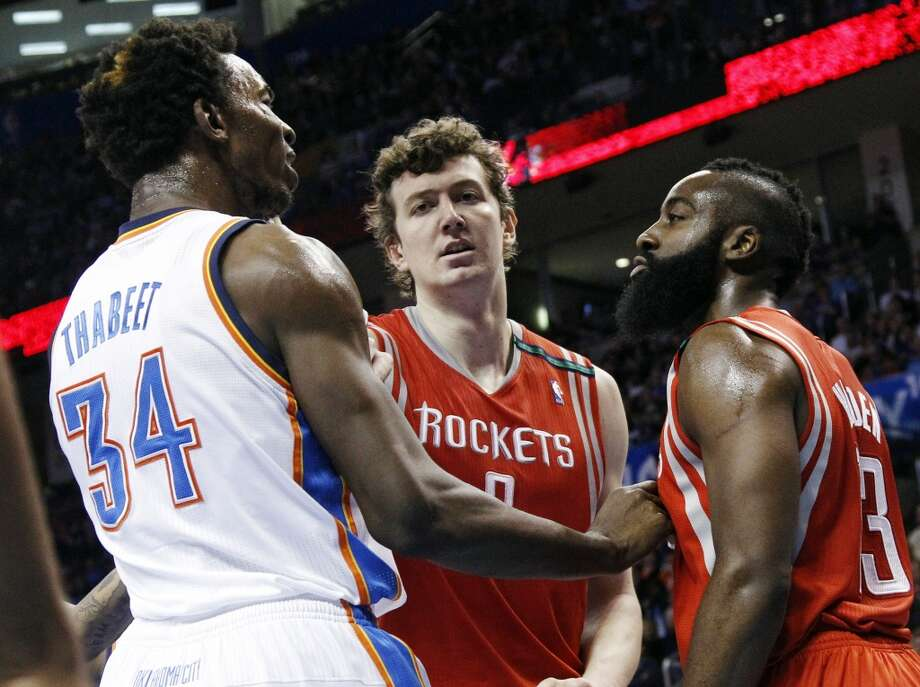 Rockets center Omer Asik (3) gets between Thunder center Hasheem Thabeet (34) and James Harden (13) in the second quarter. (AP Photo/Sue Ogrocki) (Associated Press)