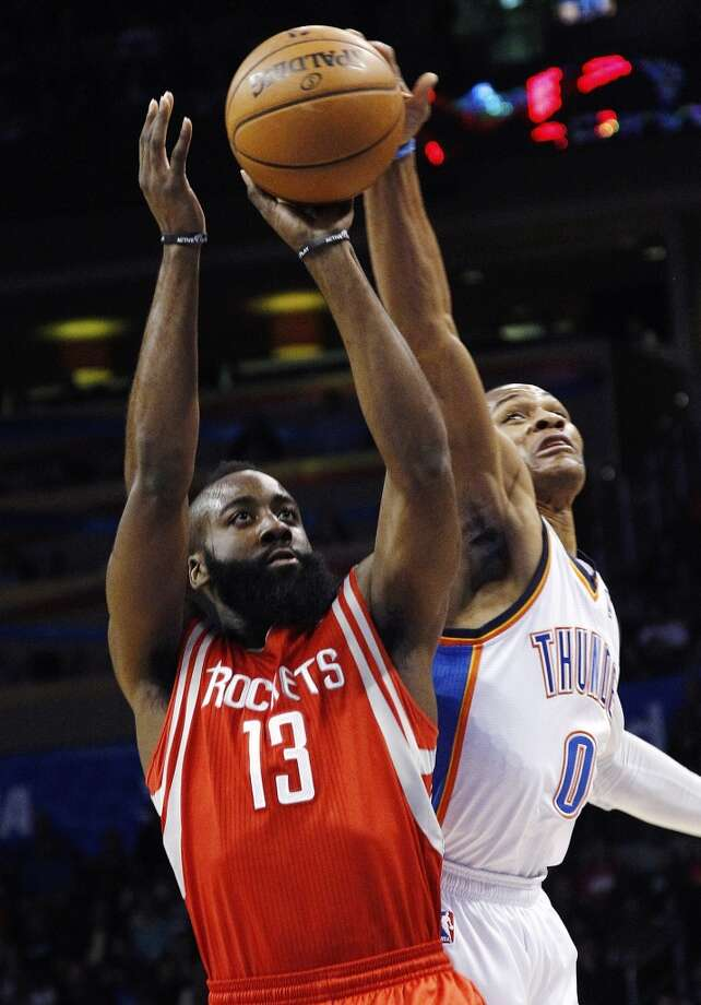 Russell Westbrook (0) reaches in to block a shot by James Harden. (AP Photo/Sue Ogrocki) (Associated Press)