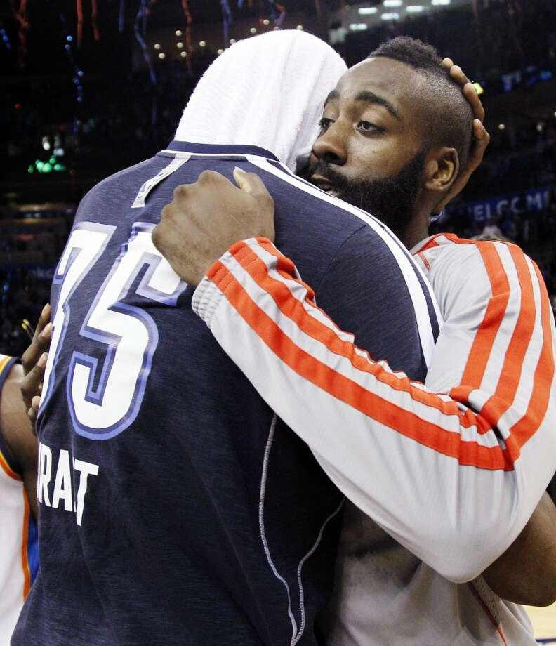 Kevin Durant, left, and James Harden, right, hug after their game. (AP Photo/Sue Ogrocki) (Associated Press)