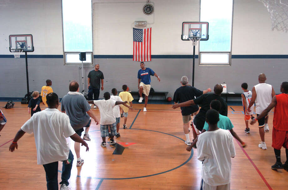 Former NBA player Allan Houston visited the YMCA in downtown Norwalk, Conn. to kick off the F.I.S.L.L. program for area youths on Thursday July 22, 2010. The program's name F.I.S.L.L. stands for faith, integrity, sacrifice, leadership, and legacy. Here, Houston leads the youngsters in some warm-up drills before starting some basketball practice. Photo: Christian Abraham, ST / Connecticut Post