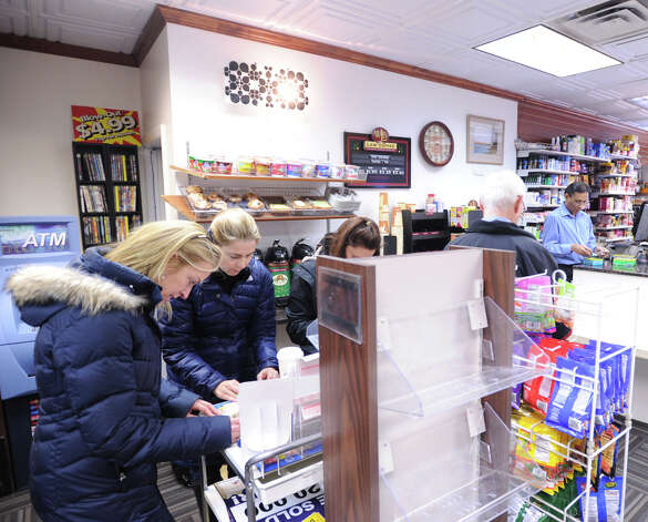With the Powerball lottery jackpot exceeding $550 million, Riverside residents Betsy Perry, left, and Lauren Lufkin, choose their numbers at Zyn's News & Cigar store on Greenwich Avenue, Wednesday afternoon, Nov. 28, 2012. At right is Piyush Sheth, the owner of the store. Photo: Bob Luckey / Greenwich Time