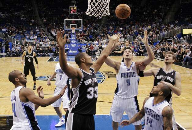 San Antonio Spurs' Boris Diaw (33), of France, battles for a rebound with Orlando Magic's Nikola Vucevic (9), of Montenegro, as Arron Afflalo (4) and Jameer Nelson (14) watch during the first half of an NBA basketball game, Wednesday, Nov. 28, 2012, in Orlando, Fla. (AP Photo/John Raoux) (Associated Press)