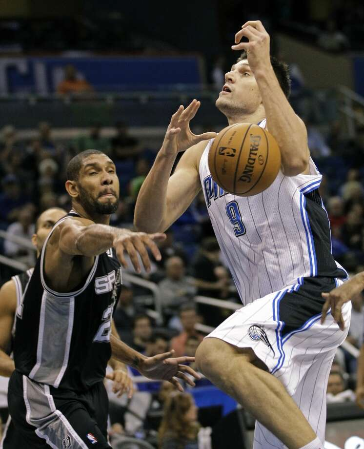 San Antonio Spurs' Tim Duncan, left, knocks the ball from the hands of Orlando Magic's Nikola Vucevic (9), of Montenegro, during the first half of an NBA basketball game, Wednesday, Nov. 28, 2012, in Orlando, Fla. (AP Photo/John Raoux) (Associated Press)