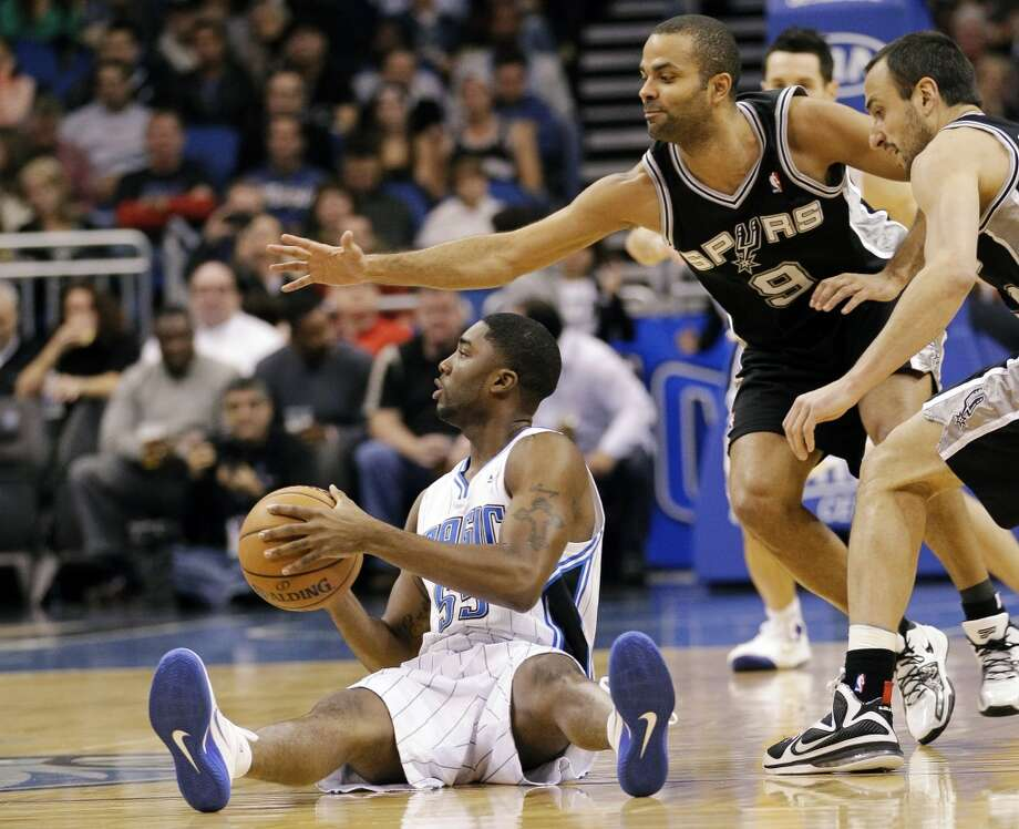 Orlando Magic's E'Twaun Moore, bottom left, looks to pass after grabbing a loose ball as San Antonio Spurs' Tony Parker (9), of France, and Manu Ginobili, right, of Argentina, try to stop him during the first half of an NBA basketball game, Wednesday, Nov. 28, 2012, in Orlando, Fla. (AP Photo/John Raoux) (Associated Press)
