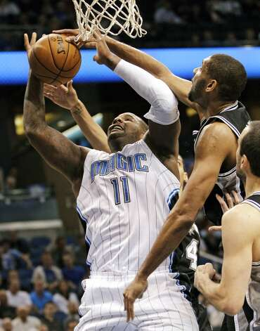 Orlando Magic's Glen Davis (11) shoots as San Antonio Spurs' Tim Duncan, center, partially blocks the shot during the first half of an NBA basketball game, Wednesday, Nov. 28, 2012, in Orlando, Fla. (AP Photo/John Raoux) (Associated Press)