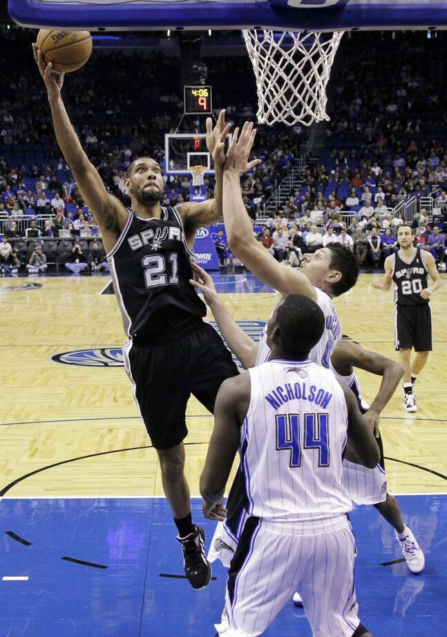 San Antonio Spurs' Tim Duncan (21) shoots over Orlando Magic's Nikola Vucevic, of Montenegro, and Andrew Nicholson (44) during the first half of an NBA basketball game, Wednesday, Nov. 28, 2012, in Orlando, Fla. (AP Photo/John Raoux) (Associated Press)