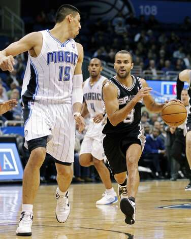 San Antonio Spurs' Tony Parker, right, of France, drives to the basket past Orlando Magic's Gustavo Ayon (19), of Mexico, during the second half of an NBA basketball game, Wednesday, Nov. 28, 2012, in Orlando, Fla. The Spurs won 110-89. (AP Photo/John Raoux) (Associated Press)