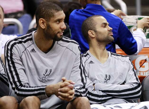 San Antonio Spurs' Tim Duncan, left, and Tony Parker, of France, watch from the bench during the fourth quarter of an NBA basketball game against the Orlando Magic, Wednesday, Nov. 28, 2012, in Orlando, Fla. The Spurs won 110-89. (AP Photo/John Raoux) (Associated Press)