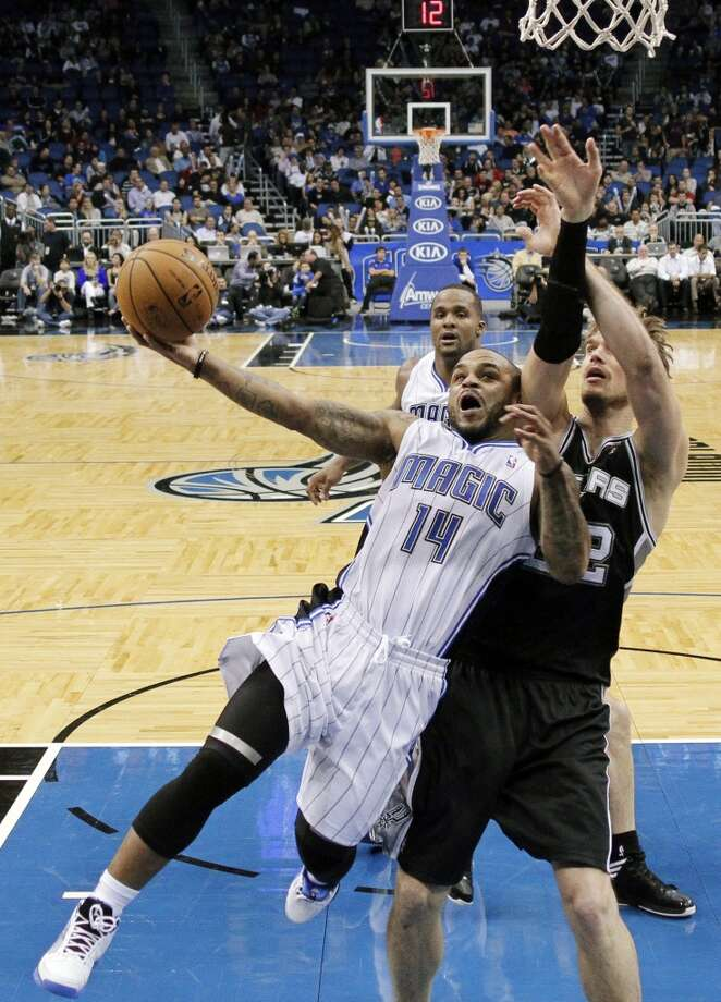 Orlando Magic's Jameer Nelson (14) drives in for a shot against San Antonio Spurs' Tiago Splitter, of Brazil, during the second half of an NBA basketball game, Wednesday, Nov. 28, 2012, in Orlando, Fla. The Spurs won 110-89. (AP Photo/John Raoux) (Associated Press)
