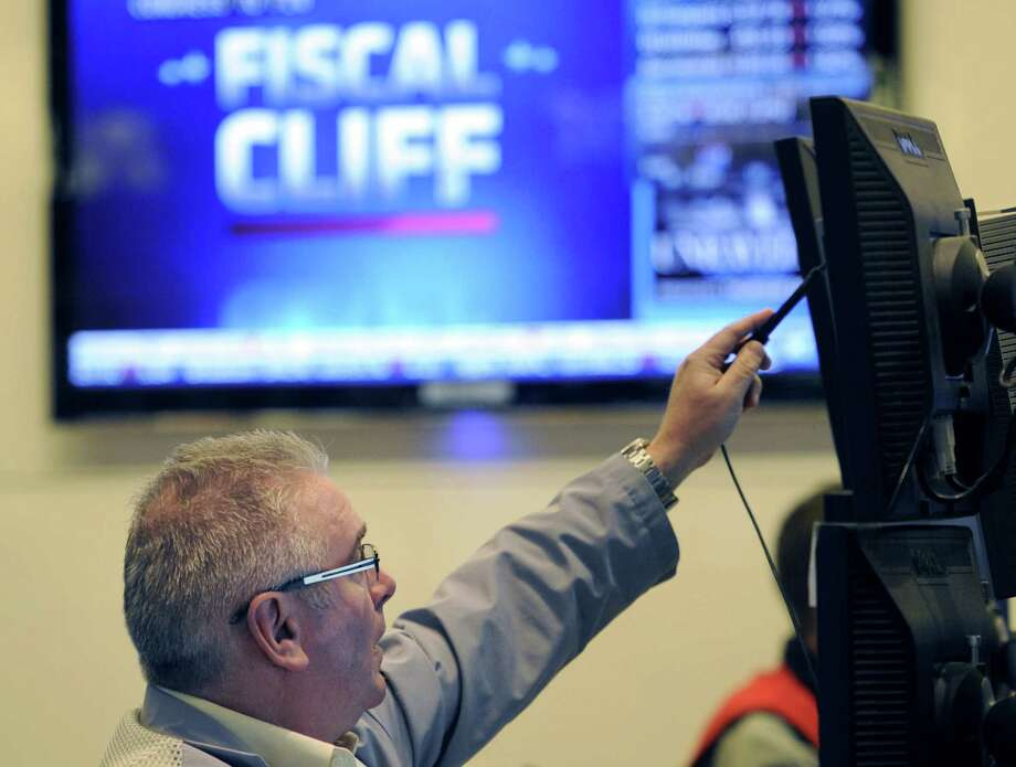 "FILE - In this Nov. 7, 2012, file photo, James Dresch of MND Partners Inc. works on the floor of the New York Stock Exchange in New York. Stocks declined for a third day on Wall Street Wednesday, Nov. 28, 2012,  as investors waited for signs of progress on the ""fiscal cliff."" (AP Photo/Henny Ray Abrams, File) Photo: Henny Ray Abrams"
