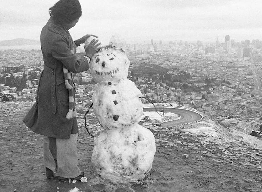 A woman on Twin Peaks makes a snowman, with a great view of the San Francisco downtown skyline. I don't know why he's smiling. Most of the snow melted by the following morning. Photo: Clem Albers, The Chronicle / ONLINE_YES