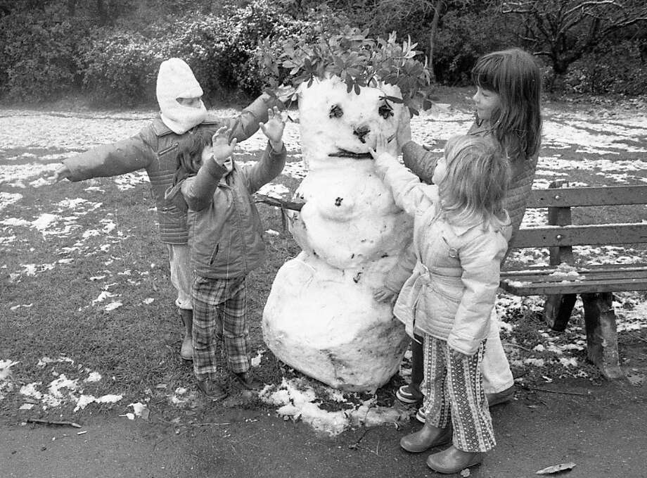 Children give this snowman a wreath crown. I put the man in quotes because this creation appears to have a pair of small but perky snow-breasts. Remember this was the 1970s -- everyone partied hard and even the snowwomen didn't wear a bra ... Photo: Clem Albers, The Chronicle / ONLINE_YES
