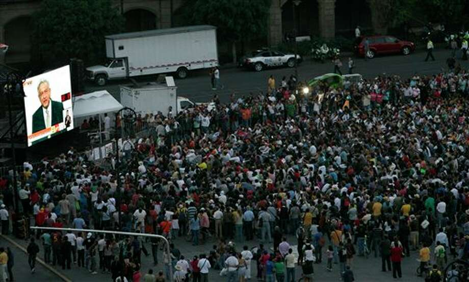 People gather to watch a broadcast of the second presidential debate on screens at Mexico City's Zocalo plaza, Sunday, June 10, 2012. Mexico will hold presidential elections on July 1. Presidential candidate Andres Manuel Lopez Obrador of the Revolutionary Democratic Party (PRD) is displayed on screen. (AP Photo/Marco Ugarte) Photo: Marco Ugarte, AP / AP
