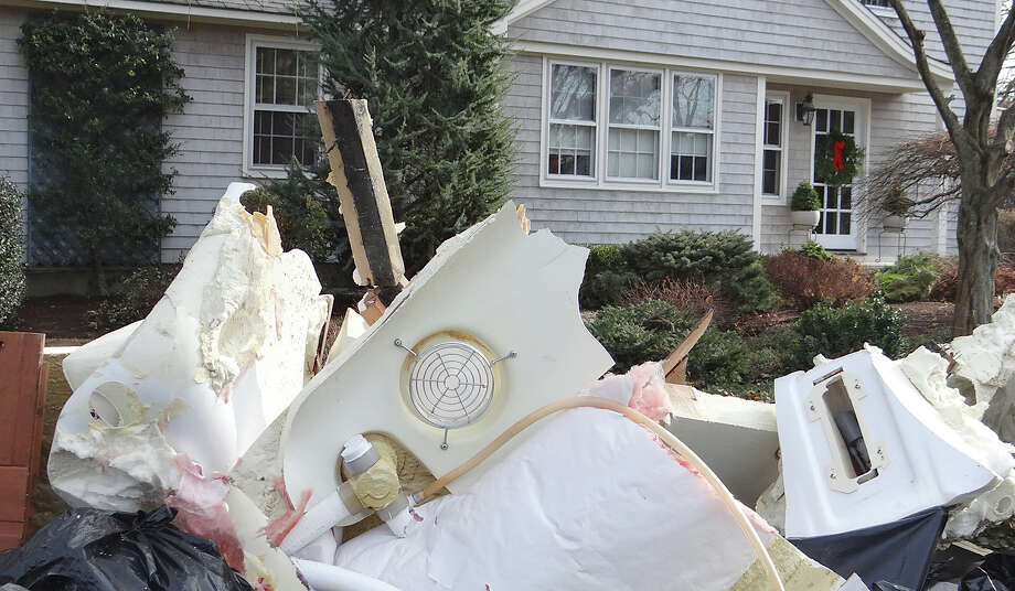 Looking past storm debris piled by the curb, a wreath adorns the front door of a Puritan Road home.  Fairfield CT 11/28/12 Photo: Mike Lauterborn / Fairfield Citizen contributed
