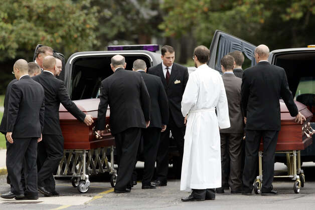 Pallbearers load the caskets in hearses after the funeral for William F. Nadvornik and Margaret Nadvornik at the St. Andrews Episcopal Church in Livonia, Mich., Friday, Oct. 7, 2005. The Nadvorniks, both 80, were two of the 19 elderly tourists from Michigan who died in the Ethan Allen boating accident in New York last weekend. The boat tour was part of a fall foliage trip that they had signed up for with one of their travel clubs. Photo: CARLOS OSORIO, AP / AP