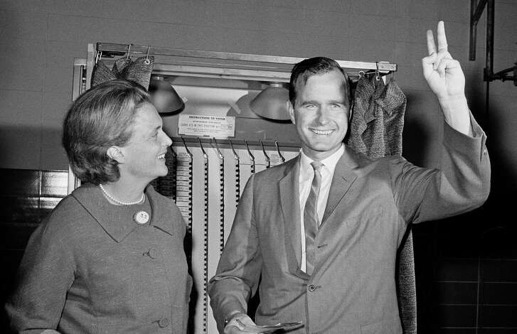 Republican Senatorial candidate George Bush shows a victory sign as he and his wife Barbara stand in front of a vote machine November 3, 1964 in Houston,Tex., just before casting their ballot.   The candidate waited an hour and a half in a long of votes that circled the Pilgrim Elementary School where the Bush's voted this morning. in Houston.    (AP Photo).