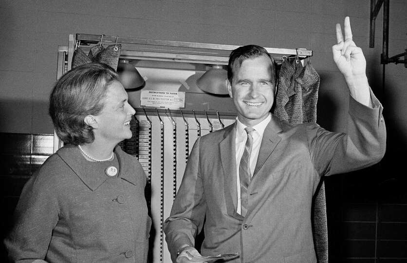Republican Senatorial candidate George Bush shows a victory sign as he and his wife Barbara stand in