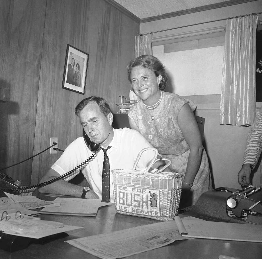 George Bush, candidate for the Republican nomination for the U.S. Senate, gets returns by phone in Houston, Saturday, June 6, 1964, as his wife Barbara, needlepoint bag on desk, beams her pleasure at the news. Photo: Ed Kolenovsky, ASSOCIATED PRESS / AP