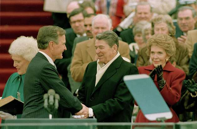 President George Bush, left, is congratulated by outgoing President Ronald Reagan after Bush took the oath of office as the 41st president of the United States on Capitol Hill in Washington, D.C., Friday, Jan. 20, 1989.  Shown at left is first lady Barbara Bush and applauding at right is Nancy Reagan.  (AP Photo/Bob Daugherty) Photo: BOB DAUGHERTY, ASSOCIATED PRESS / AP