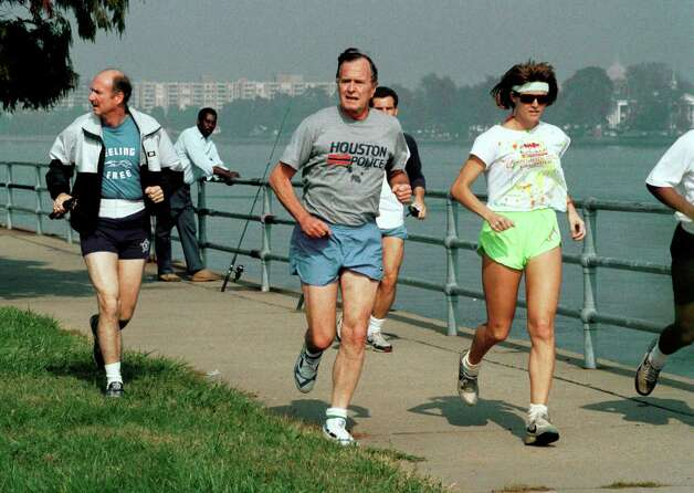 President George H.W. Bush, right, and a Secret Service agent jog by a lone fisherman Monday October 30, 1989 on Haines Point in Washington, D.C.    Bush took the short noon-time jog along the Potomac River where fishing is popular. Photo: Marcy Nighswander, AP / AP