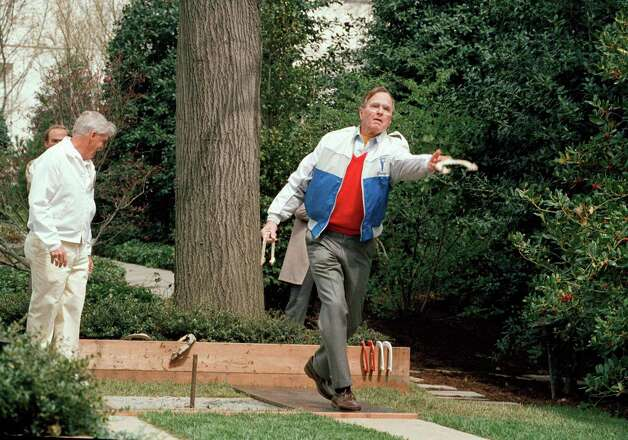 President George H.W. Bush lets loose of a horseshoe during the dedication of the new horseshoe pit  on the White House lawn Saturday  April 1, 1989 in Washington. Other people are unidentified. Photo: Barry Thumma, AP / AP